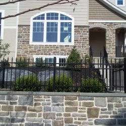 aluminum fence installed on top of a stone wall
