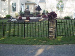 black aluminum fence with stone columns