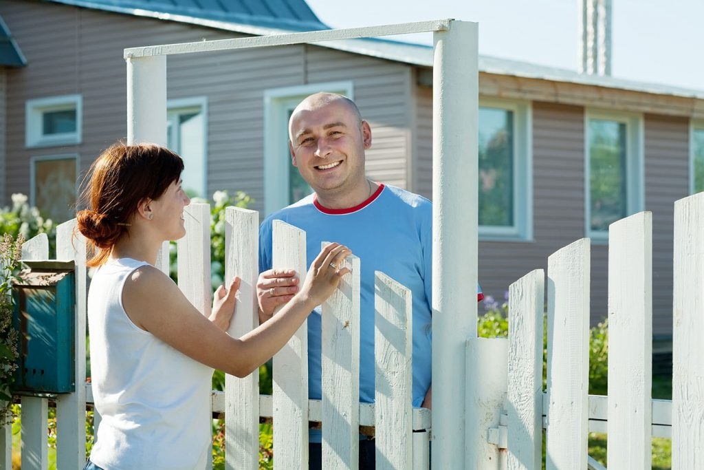 neighbors bonding over beautiful white picket fence