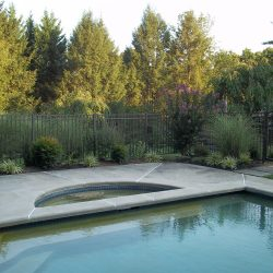 textured bronze aluminum pool fence installation protects a backyard pool