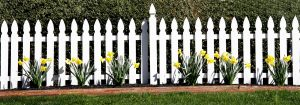 Clean vinyl picket fence with landscaping