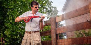 Man power washing wooden fence