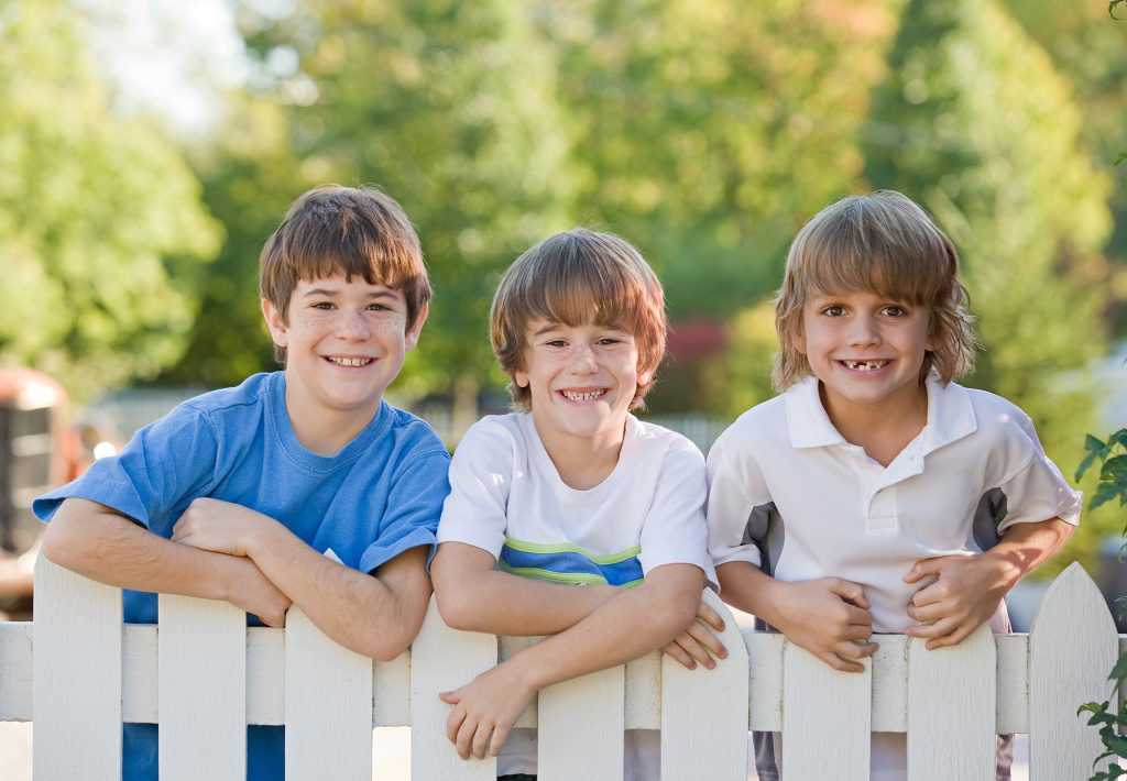 Kids on white wooden fence