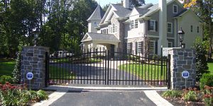 Automatic aluminum driveway gate in front of stone house