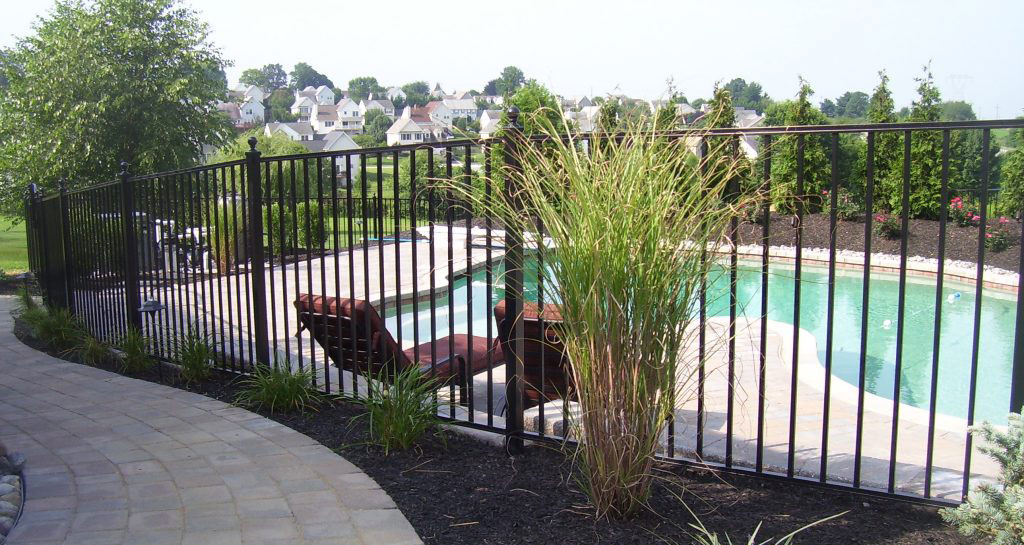 Black aluminum pool fence with landscaping