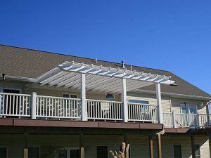 White vinyl pergola attached to house on second story deck