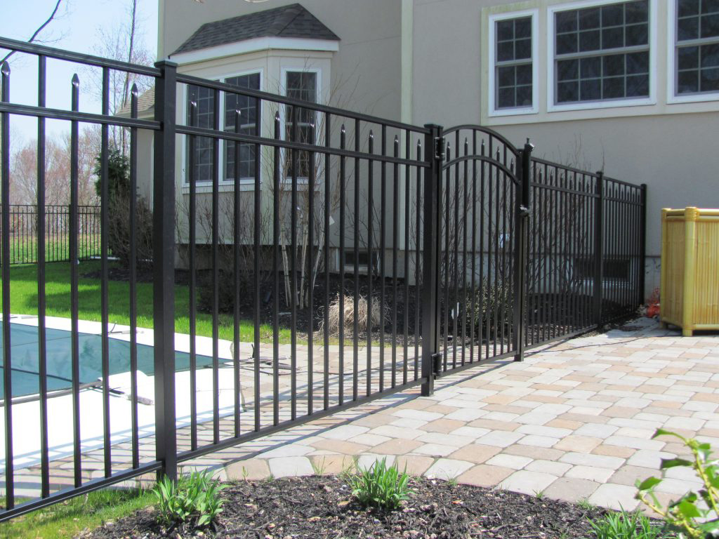A black aluminum fence surrounding residential pool