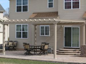 Tan vinyl pergola attached to house patio