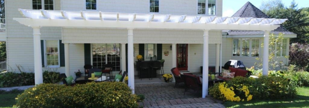 White vinyl pergola kit semi-attached to house
