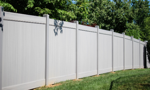Modern gray vinyl privacy fence in yard