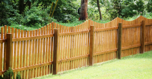 Curved top wood picket fencing in backyard