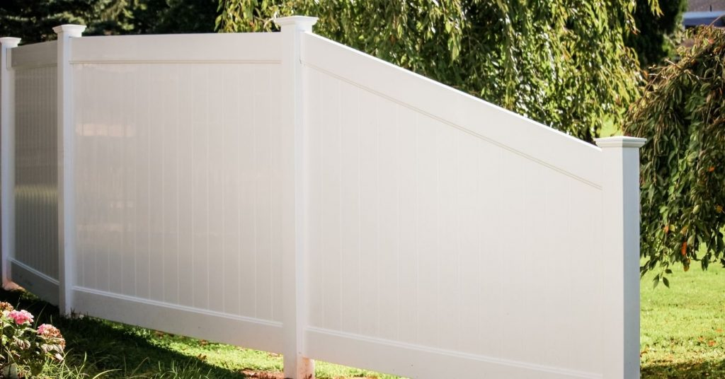White privacy fence installed on inclined yard