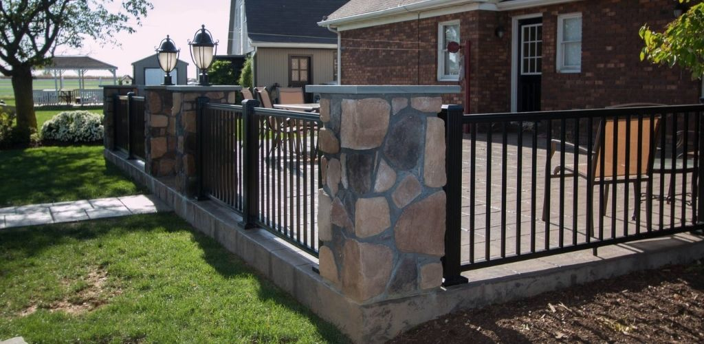 deck railing style shown in aluminum with stone pillars