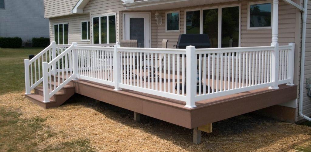 White vinyl deck railing with new tan deck